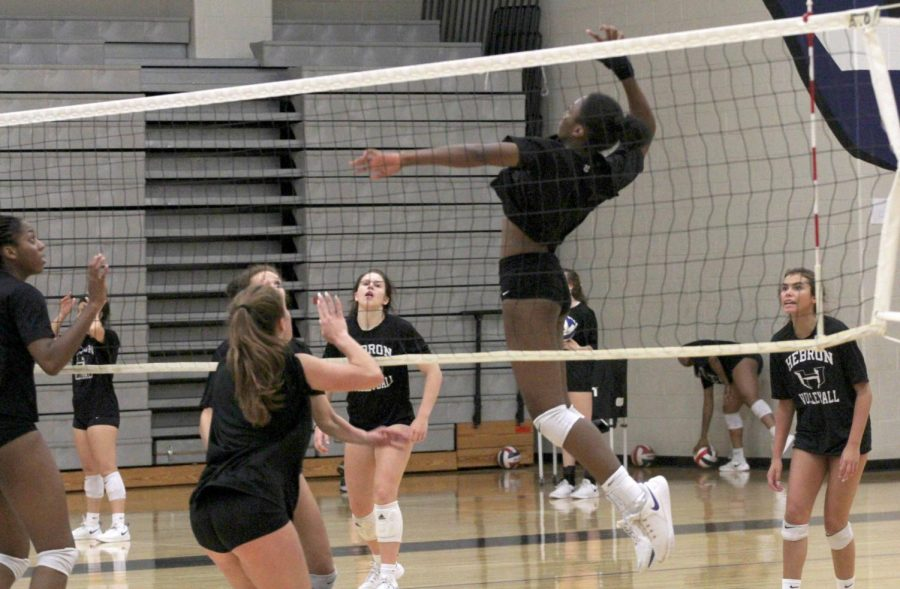 "Sophomore Lia Okkamor jumps up to hit the ball at a practice before school on Sept. 26. The team practices every week depending on the day it's either in the morning or after school. ""My life revolves around volleyball, so it gets hard to manage my other work,"" Okammor said. ""I can overcome it."""