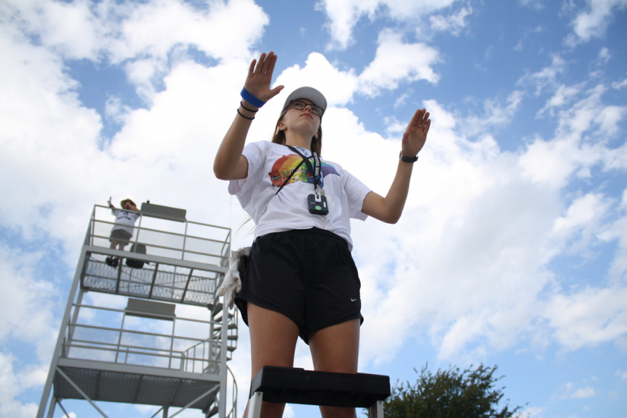 """Head drum major Abby Rieger conducts the band during morning rehearsal on Sept. 26. The band is preparing their upcoming show """"Among the Stars."""""""