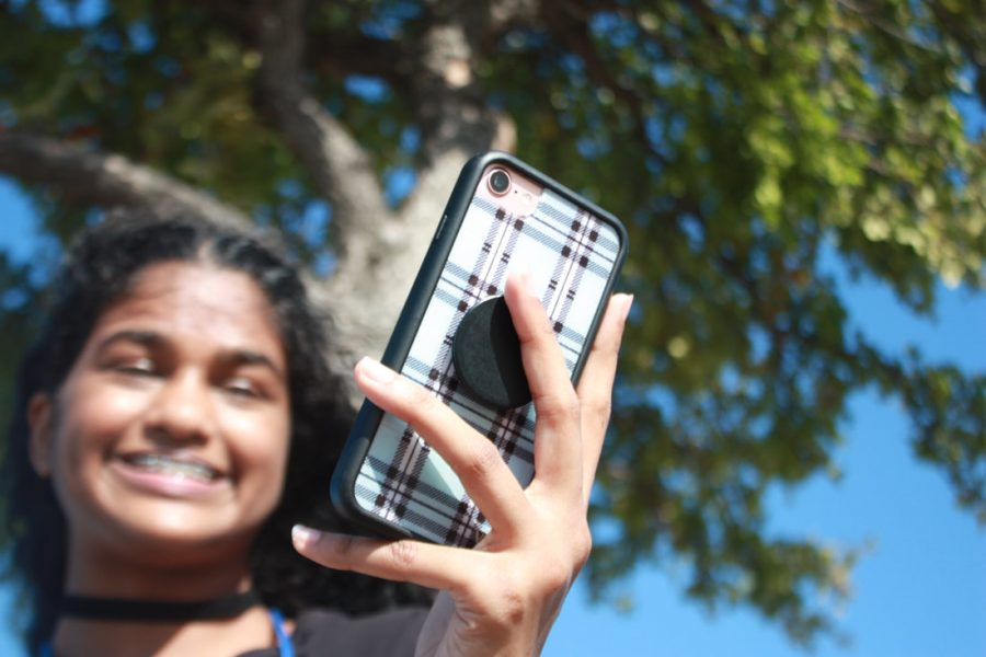 Junior Sophia Varughese takes selfies out in the sun during first period on Sept. 27. This low aperture shot was taken for a journalism assignment.