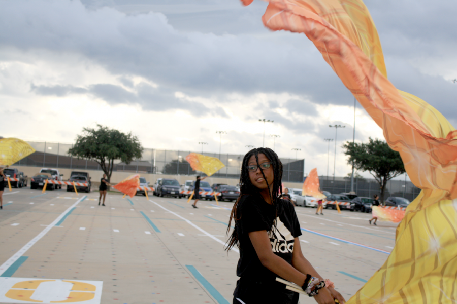 Sophomore Sannaya Williams practices with her flag. The color guard was preparing for the homecoming football game on Sept. 27.