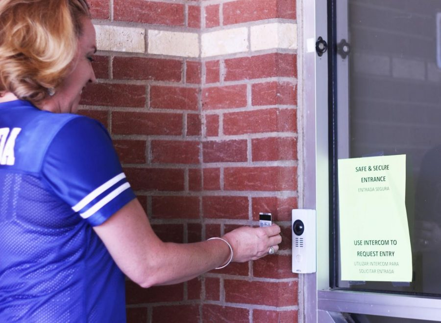 "Parent Kimberly Estrada shows her ID to the video doorbell so that she can enter the school for the pep rally. Estrada has two kids that go to Hebron, and even though the whole process of getting into the school is tedious, she feels assured that they are safe inside the building. ""It makes me feel safe as a parent to know that my kids are in a place where security is held in high regard,"" said Estrada."