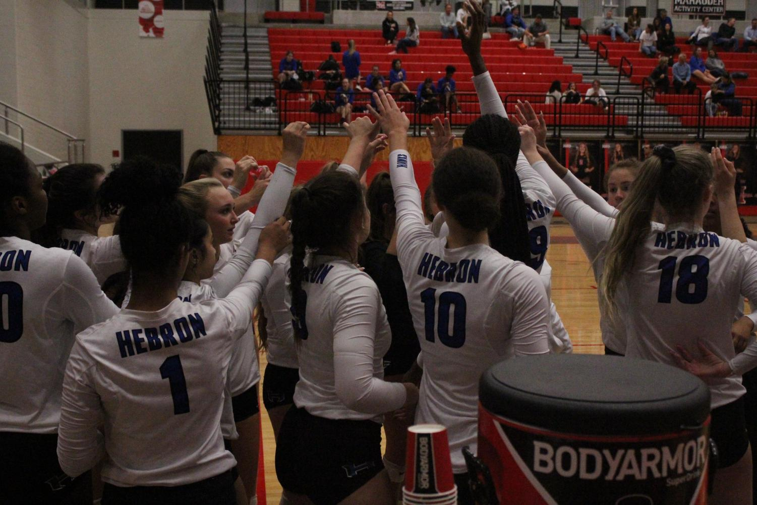 The volleyball team raises their hands and chant before their game against Marcus on Oct. 11. This is a tradition for the Hawks before they begin every game.