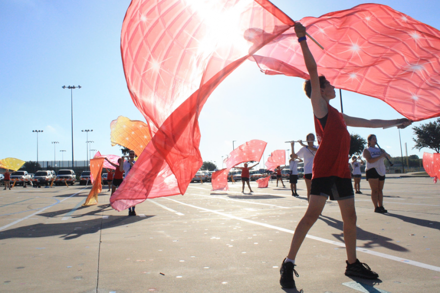 Color guard member Ethan Connolly practices part of his flag sequence during morning rehearsal on Sept. 27. Connolly is in his second year of performing with the Hebron Colorguard.