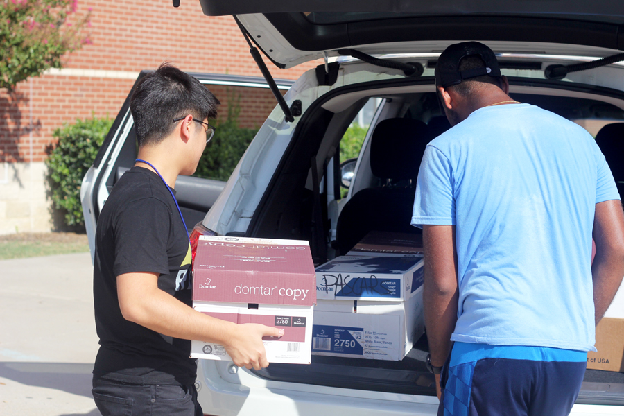 Seniors Phillip Ng and Allan Jacob load boxes filled with donations into Allan's car. After loading the supplies into the car, the seniors went shopping with the remaining money.