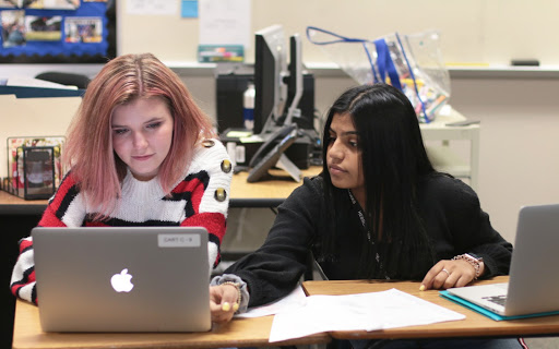 "Sophomores Maddison Smith and Saba Ali look over cases for their debate topic. Debate has practice every Tuesday after school from 4:00 p.m to 6:00 p.m. ""I hope to become better at managing my time better during rounds and maybe being more exaggerated when talking and giving speeches,"" Ali said."