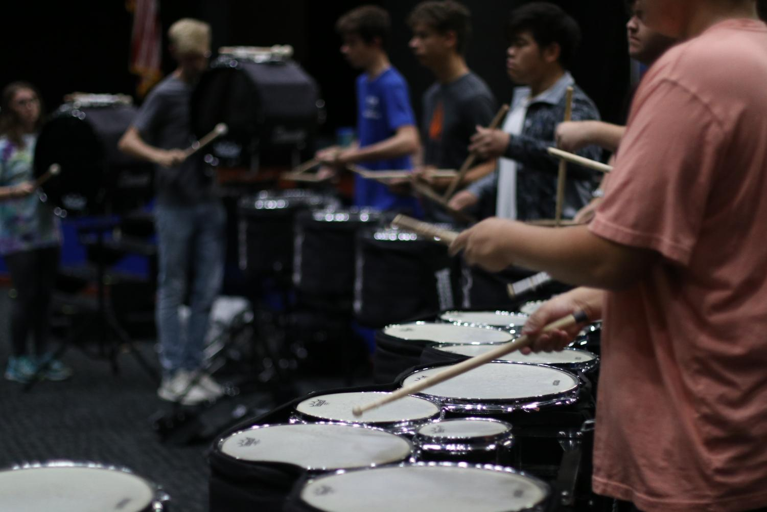 Drumline rehearses before school in the auditorium due to bad weather.