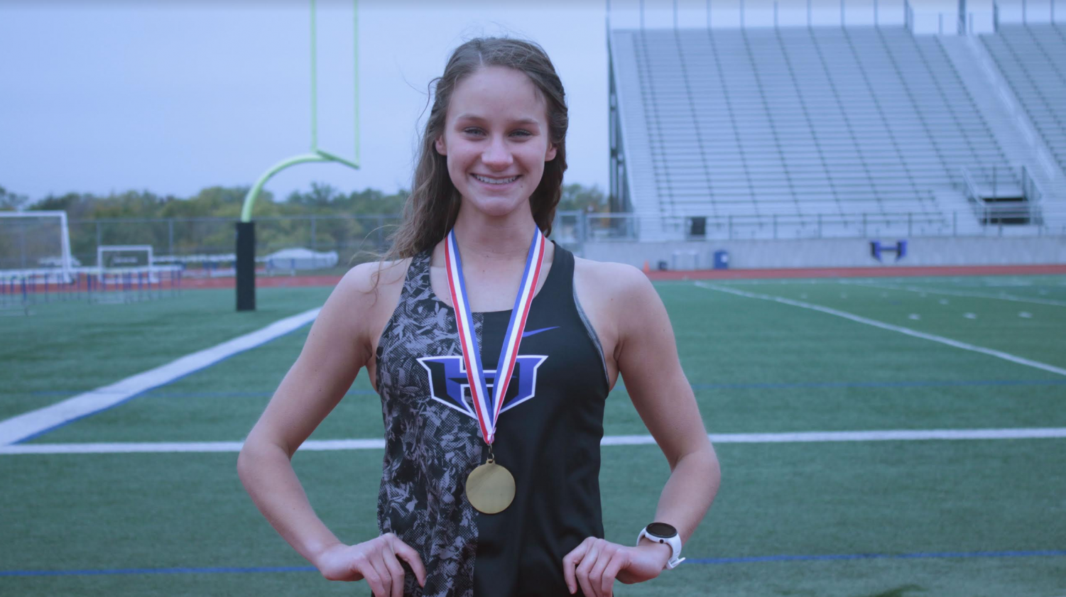 Junior Keaton Morrison poses on the track in her racing singlet with the medal she received at the district meet. Morrison will travel to Round Rock to compete at the state meet on Nov. 9 as an individual.
