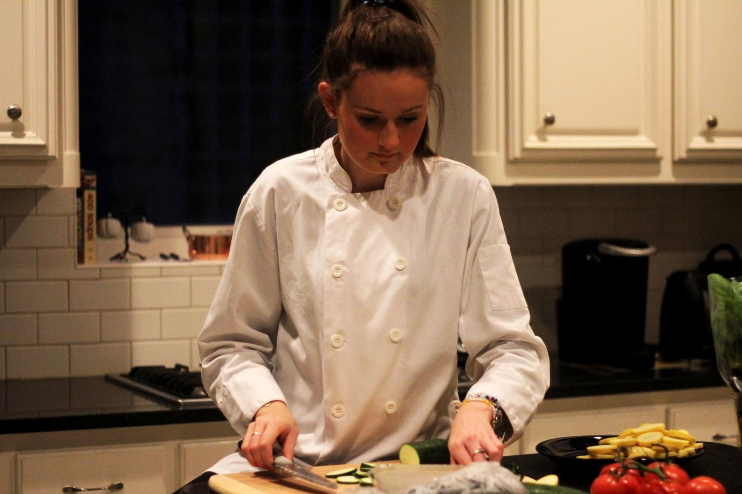 "Junior Tara O'Donnell cooks ratatouille, a stewed vegetable dish, in her kitchen. She wears the chef's coat that she won while on Chopped Junior. ""I love to cook different dishes,"" O'Donnell said. ""My favorites to cook are mediterranean, french and asian dishes."""