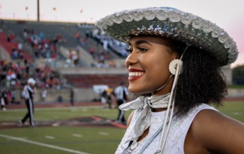 Senior Mariah McCardell smiles to the crowd during a football game at Coppell on Oct. 4. McCardell is the first African-American captain for Silver Wings.
