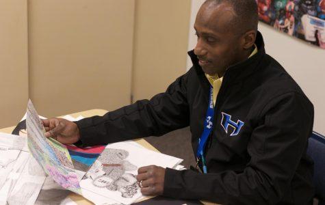 Art 1 teacher Valento Mennsfield grades his student's art pieces. This is Mennsfield's first year working as an art teacher at a high school.