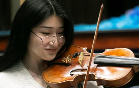 "Senior Grace Kang practices her part for the upcoming musical. Although she plans to study visual art in college, she hopes to continue playing violin in future musical performances. ""If I have the opportunity to get paid to play in different musical performances, that would be awesome,"" Kang said. ""I would definitely sign up for that."""