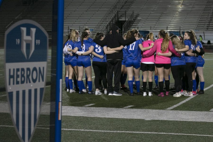 "Varsity gathers in a huddle before the kick off. It is tradition for someone to lead the team in prayer before the match, and after the prayer, the girls yell a chant that starts, ""Matthew, Mark Luke and John"" and blesses the game."