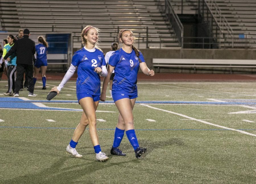 """Juniors Olivia Hunt and Ava Meyer walk to the bench after the game ends. Vaughn tried to give everyone a chance to play during the match, including underclassmen. """"All the girls practiced hard and wanted to play, so if you have time to add them in, you want to give them quality minutes,"""" Vaughn said."""