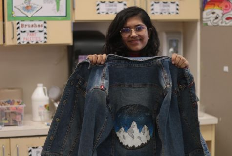 "Sophomore Unaiza Khakoo poses with a jean jacket she painted. Khakoo will sell art pieces like this to raise money for an organization named Art From the Streets as a part of her Girl Scout gold award. ""The gold award for Girl Scouts is the highest project you can do and the highest honor you can achieve,"" Khakoo said. ""In the project girl scouts are told to choose an issue they see in their community and find a way to combat it."""