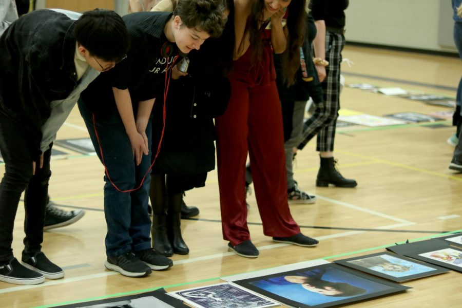 Seniors John Pham, El Champion, Lauren Santaella and junior Claire Song admire a piece on the gallery floor. The floor was split into different divisions, 1-4, based on the amount of art credits a student has.