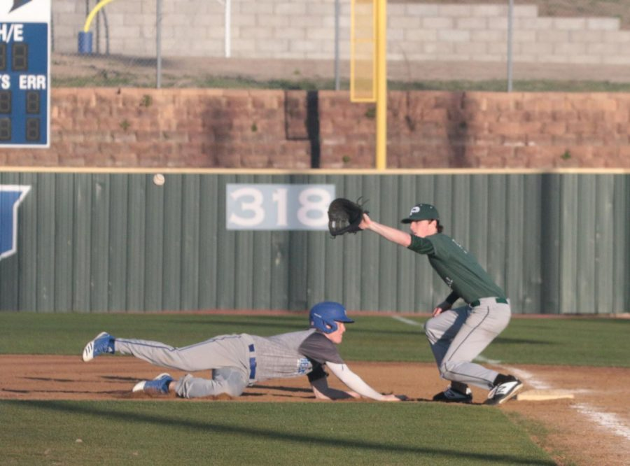 Junior Trent McCown dives back into first after the pitcher tries to pick him off at the Hebron vs. Prosper scrimmage on February 24. Varsity practices during fourth period.