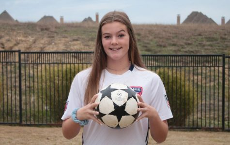 """Freshman Eleanor Hays poses with a soccer ball. She plays soccer for the FC Dallas U-16 development academy for Girls. """"The development academy focuses on developing our skill and our talent so we can go farther with soccer into college and possibly professionally,"""" Hays said."""