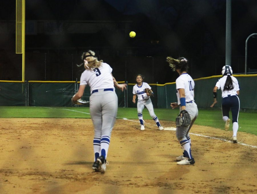 Junior Madeline Carter throws the ball to senior Zebedee Gonzales to get the out at first base. A second baseman, Gonzales ran to cover first for senior Ira Kang when she came in to field a bunt.