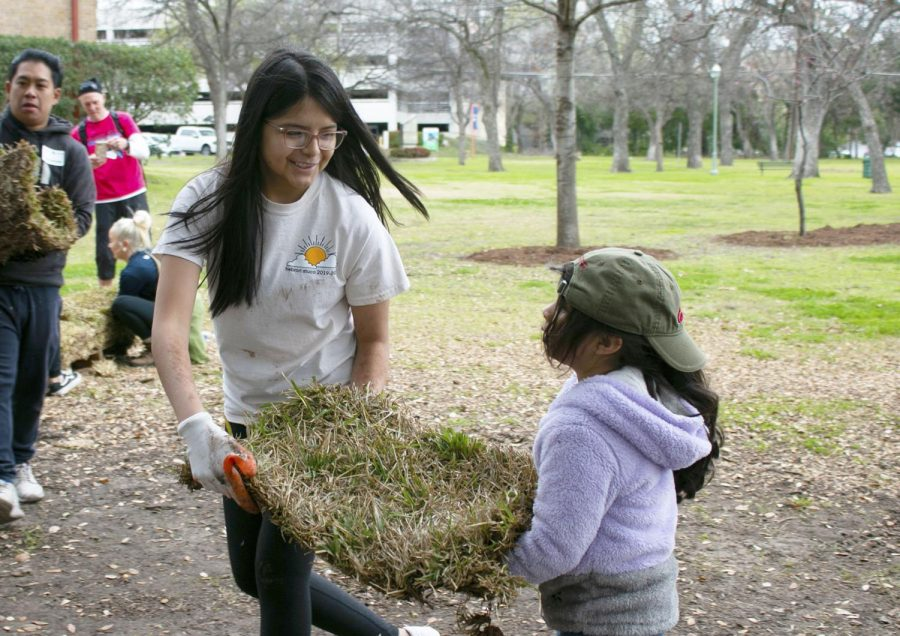 Sophomore Deedra Torres helps a girl carry sod to place on the ground. Many other people came out to help, especially from local churches, and the event was also briefly featured in The Dallas Morning News.