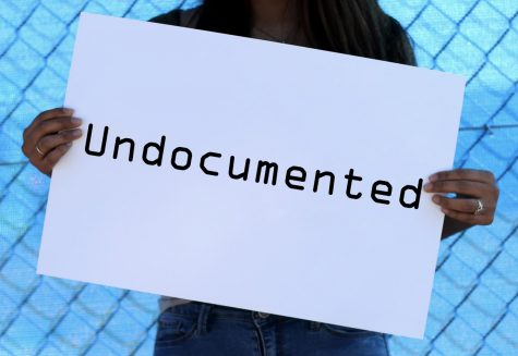 "Lin holds a sign with the word ""undocumented"" on it."