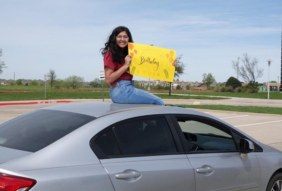 "Sophomore Unaiza Khakoo sits on the roof of the car while holding the poster she made for Wieber. She and Wieber have been friends since eighth grade. ""We became really good friends through theater,"" Khakoo said. ""We just bonded and have continued that relationship throughout the years. She has helped me with a lot, and I have helped her with a lot and it is amazing to have a friend who is always there for you like Remy is for me."""