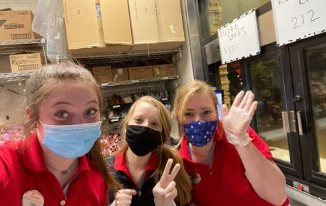 """Junior Ellory Liles and two of her coworkers pose together for a photo with their required face masks and gloves. """"We are all required to wear face masks and gloves no matter what position we are inside the restaurant,"""" Liles said."""