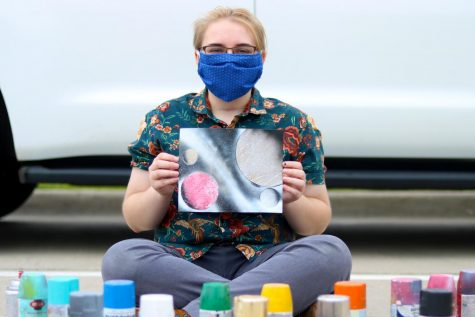 Senior Makena Butler poses with one of her spray paint pieces. She is wearing a mask to protect against Covid-19.