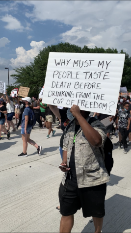 Man marches with sign that says 'Why must my people taste death before drinking from the cup of freedom?