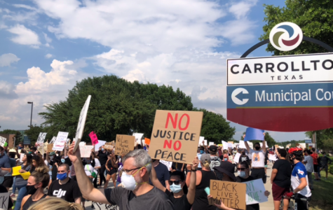"Protesters march with signs in front of the Carrollton Municipal Court. The protest was in solidarity with other Black Lives Matter protests across the nation, but there are many other ways to support the BLM movement. ""Try to research as much as you can,"" senior Jacquelyn Burrer said. ""Read as many things as you can to learn about the reforms that need to happen. Obviously, not everyone will want the same level of reform, but there is a common goal in the movement: that something needs to change. As long as people are getting involved and continue to speak out about what is important, we can prioritize changing the system."""