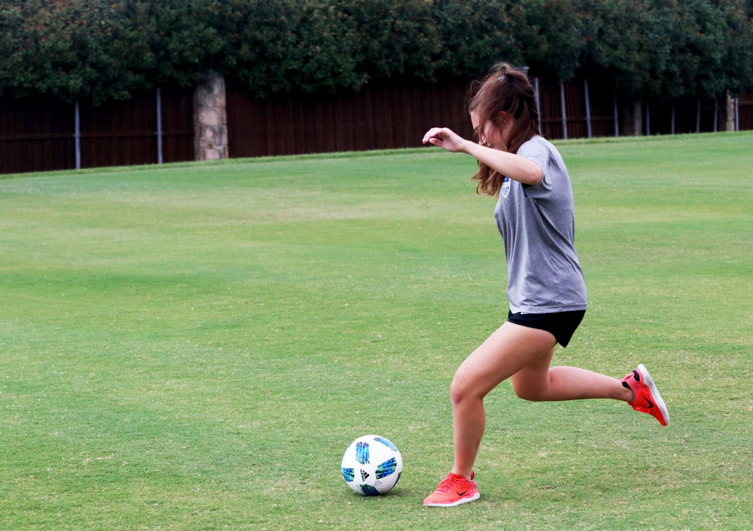 Senior midfielder Ava Meyer practices shooting drills outside of school. The team practices everyday in order to prepare for the upcoming soccer season.