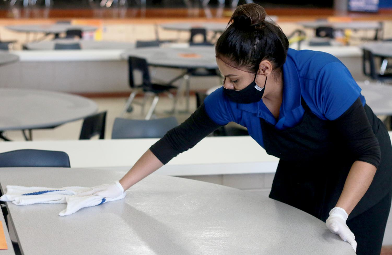 """Cafeteria worker Nayely González wipes down cafeteria tables between lunches. Cafeteria workers now conduct much more extensive cleanings, in response to COVID-19. """"I was really worried about lunch personally when I envisioned coming back to school,"""" counselor Dr. Justin Fields said. """"My initial thoughts have been good."""""""