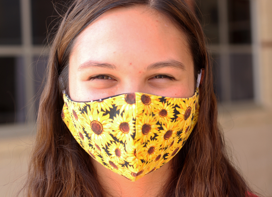 Junior Audri Fleming poses in her handmade mask. Fleming has made a variety of masks for her and her family including both sunflowers themed and Halloween themed.