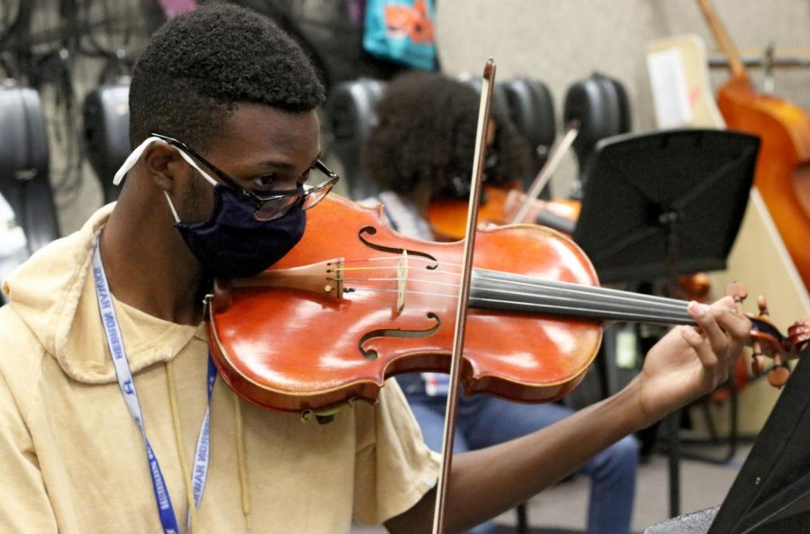 "Junior KeJuan Thompson plays ""Mission Impossible"" with the rest of the orchestra during practice. Thompson has been a part of the orchestra program for five years."