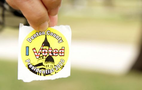 Voter Samina Ismail holds out her sticker that she received after voting at the Rosemeade Recreation Center. After scanning in their ballots, voters receive a sticker recognizing that they voted.