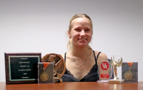 """Senior Kasia Drewniak poses with awards she has received during her time in debate. Drewniak started debate her freshman year. """"I have a Polish mom and she was looking at stuff that would look good on my college applications when I was in eighth grade,"""" Drewniak said. """"She [said] 'Kasia, you talk way too much, you should join debate.' So that's what I did. And then I grew to love it a lot, which is crazy because I wasn't even going to do it if it wasn't for that."""""""