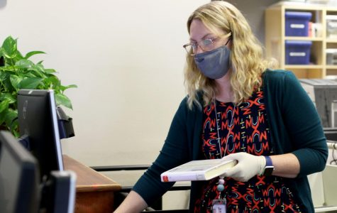 "Librarian Kristi Taylor puts on gloves while wearing a mask, before checking books into the library system. Taylor said she wishes more students would say hello and strike up a conversation with her. ""Speak when spoken to,"" Taylor said. ""Not everyone knows how to talk to someone who's friendly. Say hi. I'm friendly and I talk a lot."""