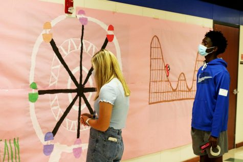 Student council members seniors Dexter Mitchell and Sydney Stafford work to finish setting up decorations for homecoming. Student council is in charge of planning and decorating the school for important events.