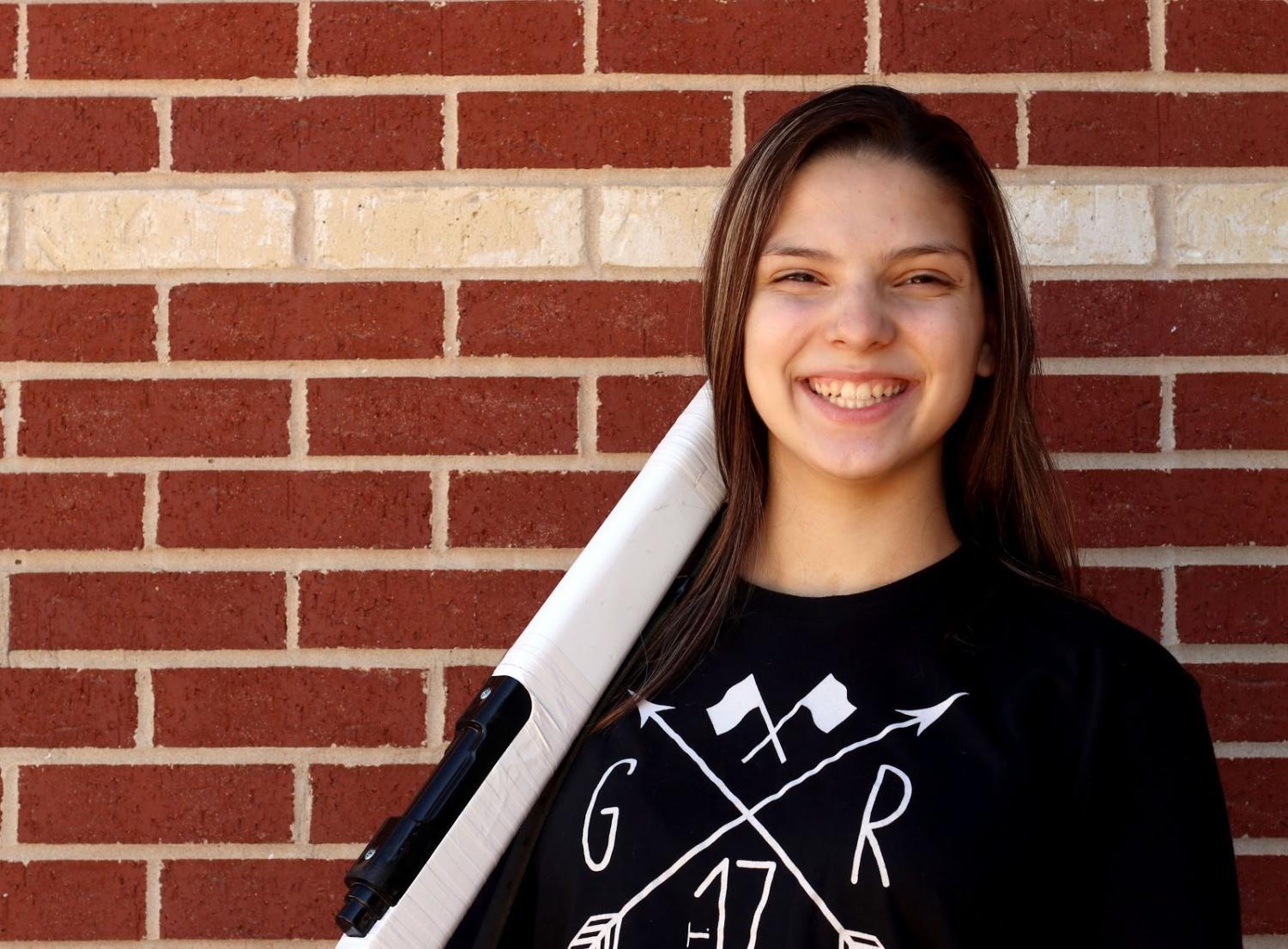 """Senior Anabel Sanchez stands outside the gym with her rifle. As one of the color guard captains, Sanchez has had to adapt to her role as a leader due to COVID. """"It's been difficult to adjust with covid rules, but just being around my team is what makes my experience better,"""" Sanchez said."""