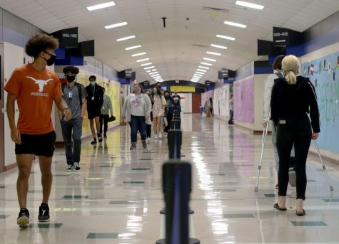 Students walk on either side of the hallway to ensure less face to face contact with each other. The Hebron Administration put the one-way walking lanes in the hallways to prevent the spread of COVID-19 at the beginning of the in-school year