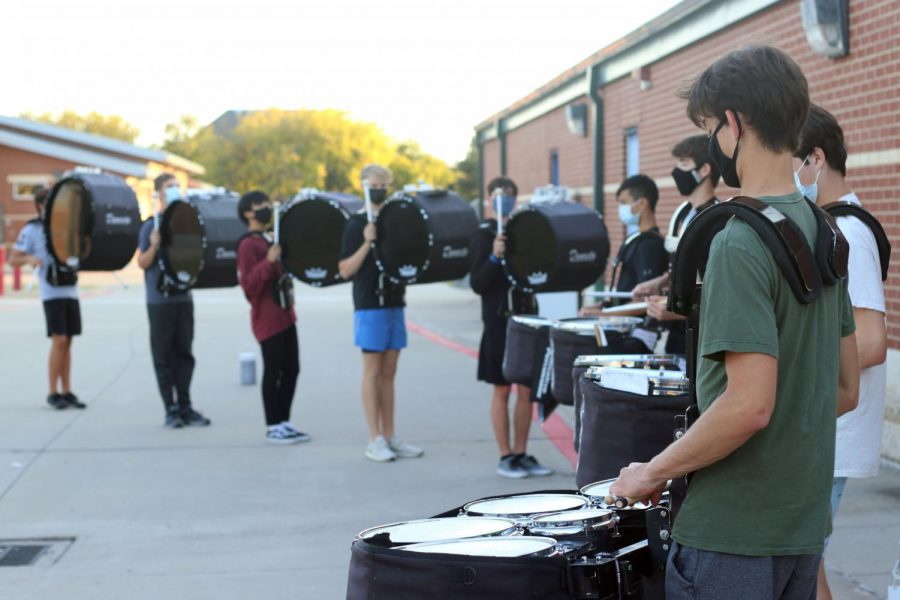 The battery warms up prior to rehearsal on Nov. 6. The battery is a specific part of the drumline that marches their instruments on the field. Hebron's battery is made up of bass drums, snare drums and quads.
