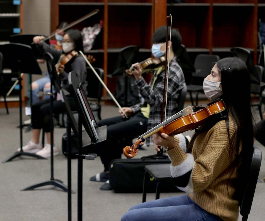 Senior Vaneeza Moloo rehearses during her third period orchestra class. Students are spaced apart and wearing masks while they practice.