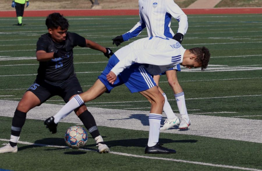 Senior Cayden Casburn weaves the ball through the legs of an opponent following a throw in. This is Casburn's second year starting as a centre back on varsity.
