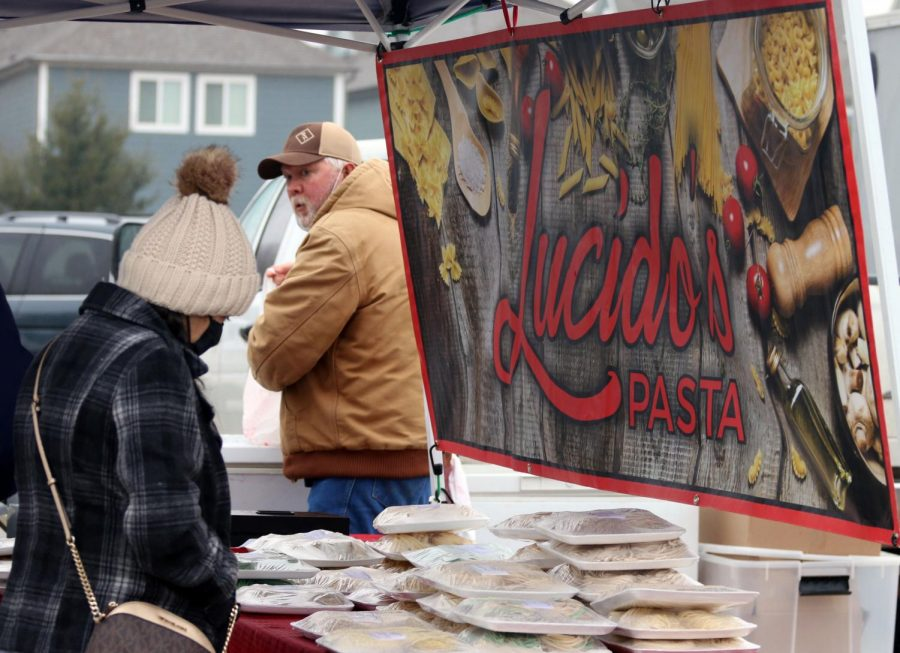A customer browses through the different kinds of pasta available at Lucido's Pasta stall. Over the years they have started to include gluten-free and whole wheat options in their pasta line.
