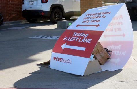 A sign is weighted down next to the CVS drive-thru, dividing the lanes. COVID-19 testing is offered at CVS locations; scheduling an appointment is required prior to getting tested.