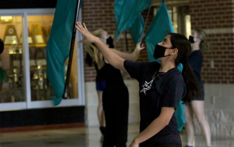Color guard captain senior Karen Lopez catches her flag during class Feb. 5. Lopez has been a captain for two years and performed with the varsity group last year.