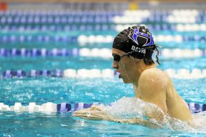Junior Tyler Davis swims the breaststroke during morning swim practice at the Westside Aquatic Center. The team swims laps at the beginning of practice to warm-up and for training.