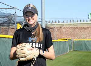 Senior Riley Nicholson poses outside the softball field with her glove. Nicholson has been playing softball for the last 8 years and has committed to play in college too.