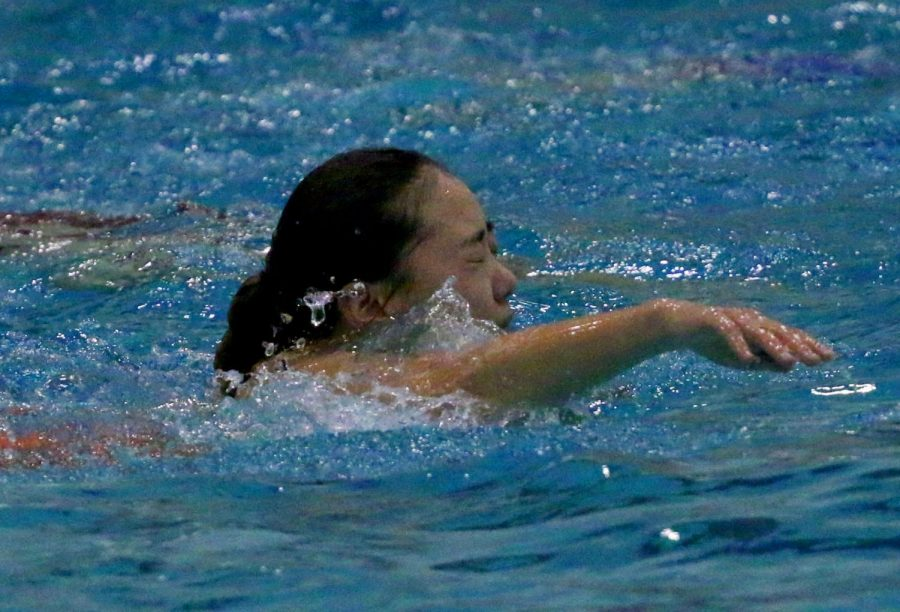 Freshman Mollie Cho practices a freestyle stroke during morning practice at the LISD Eastside Aquatic Center. After dryland workouts, the team warms up in the pool with laps.