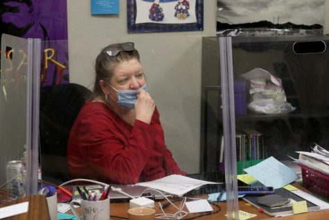 Becky Bertrand pulls up her mask while teaching her English II class behind a desk shield.