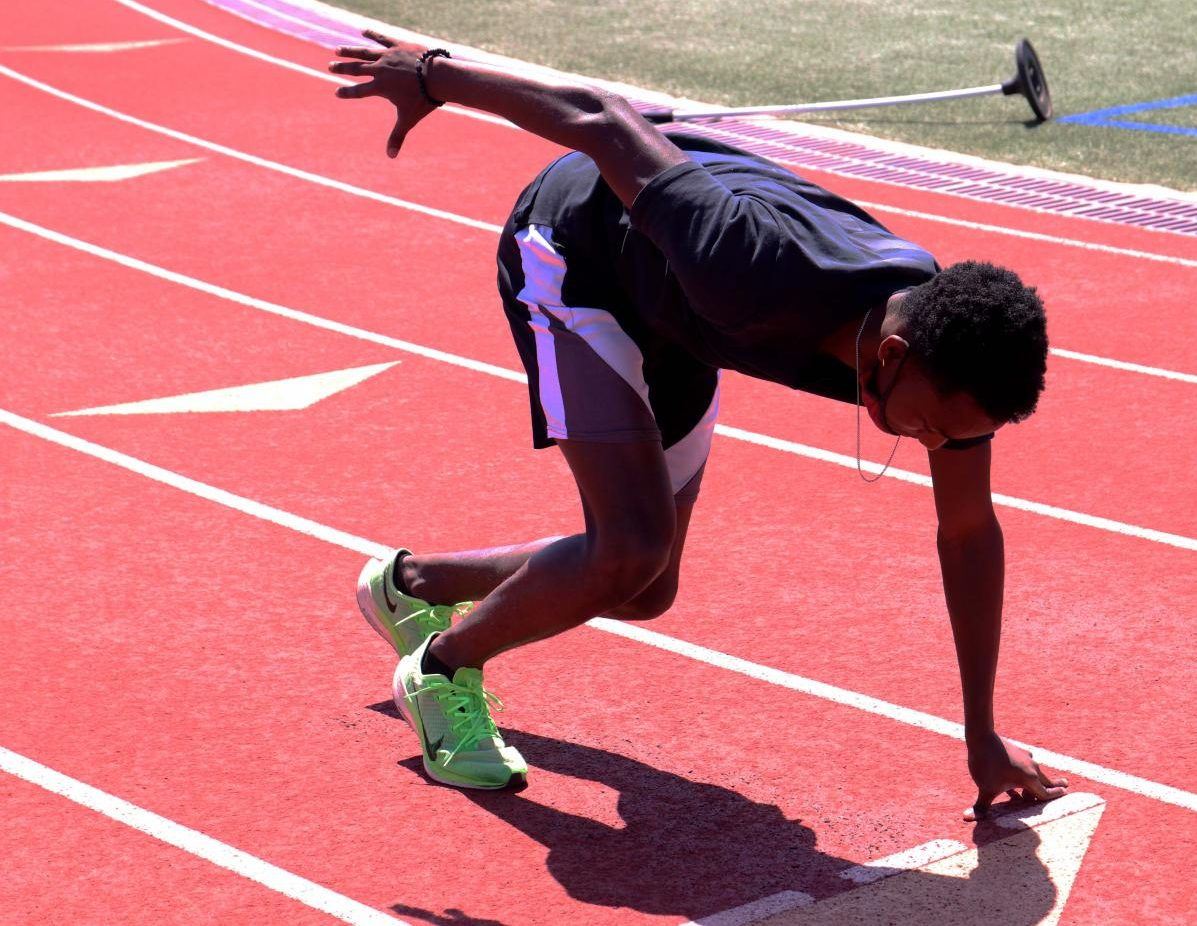 Senior Perry Aubrey gets in his starting position in preparation for the practice 100-meter run. The team practices every day during fourth period.